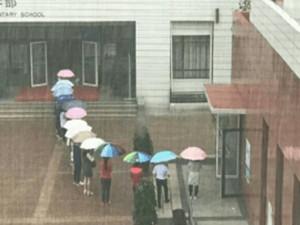 老师排队搭起伞廊 暖心举动为学生撑起一片天